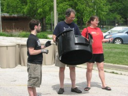 Volunteer Phil Busch assists two customers who purchased a compost bin.