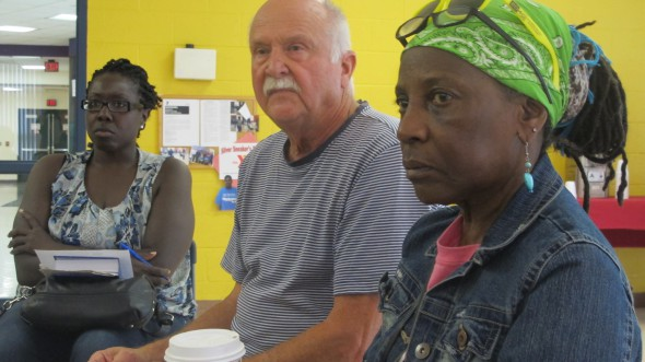 Participants listen as a community member shares a personal story about gun violence. (Photo by Andrea Waxman)