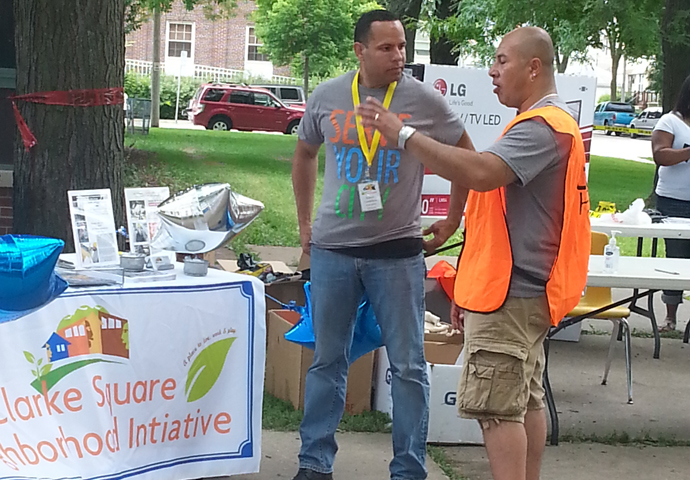 Ramon Candelaria, executive director of the Clarke Square Neighborhood Initiative, chats with volunteer Anthony Mercado during Serve Your City Day. (Photo by Raina J. Johnson)