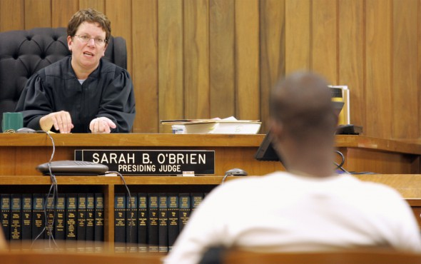Dane County Circuit Judge Sarah O'Brien speaks to a graduate of the drug court program before awarding his diploma in this 2005 photo. O'Brien ran the specialty court in Madison until her retirement in 2012. She says participants have been disproportionately white, a disparity the court is attempting to address. - Jaron Berman / The Racine Journal Times