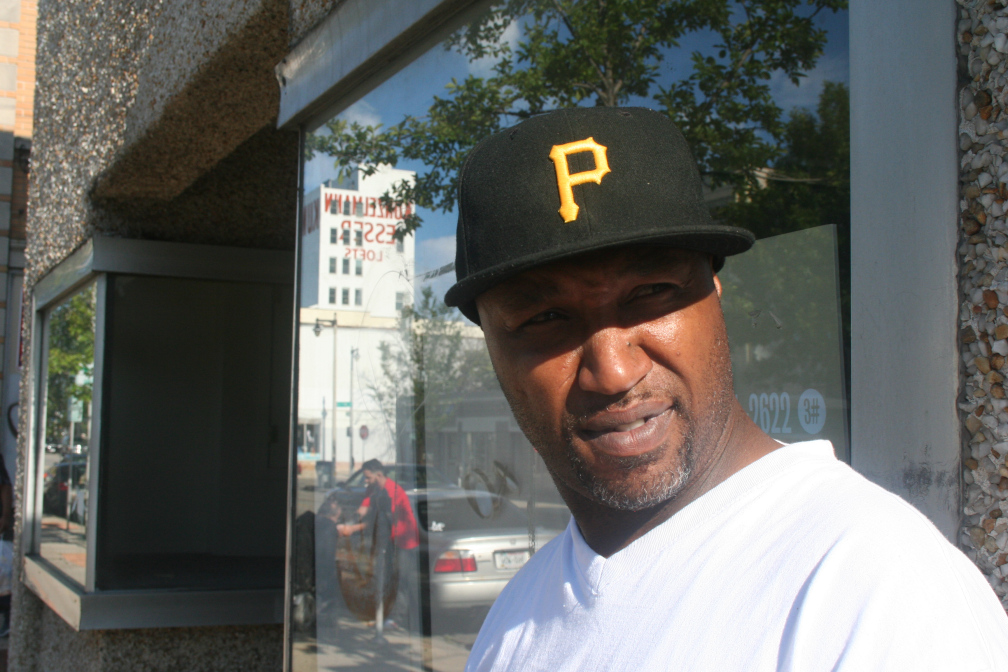 Farence Rogers stands in front of a shop window near 9th & Mitchell.