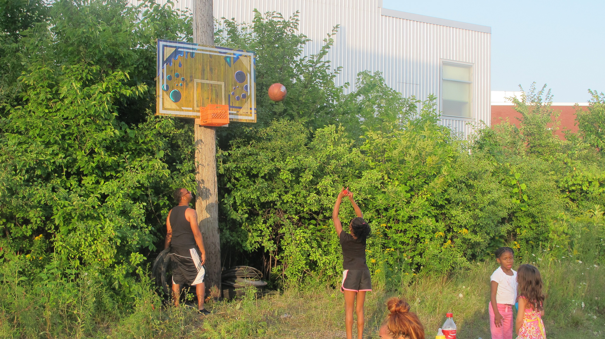 Vedale Hill's daughter Jazale shoots baskets at his hoop crate as he waits to catch the ball. (Photo by Andrea Waxman)