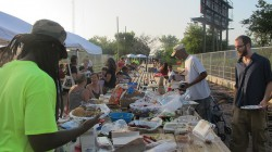 Harambee and Riverwest neighbors shared a community potluck dinner at a 100-foot table set up on a pedestrian bridge at the end of the artery. (Photo by Andrea Waxman)