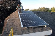 Workers install solar energy equipment on a roof in the Burnha