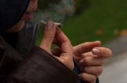 Young girl wearing leather jacket smoking a joint