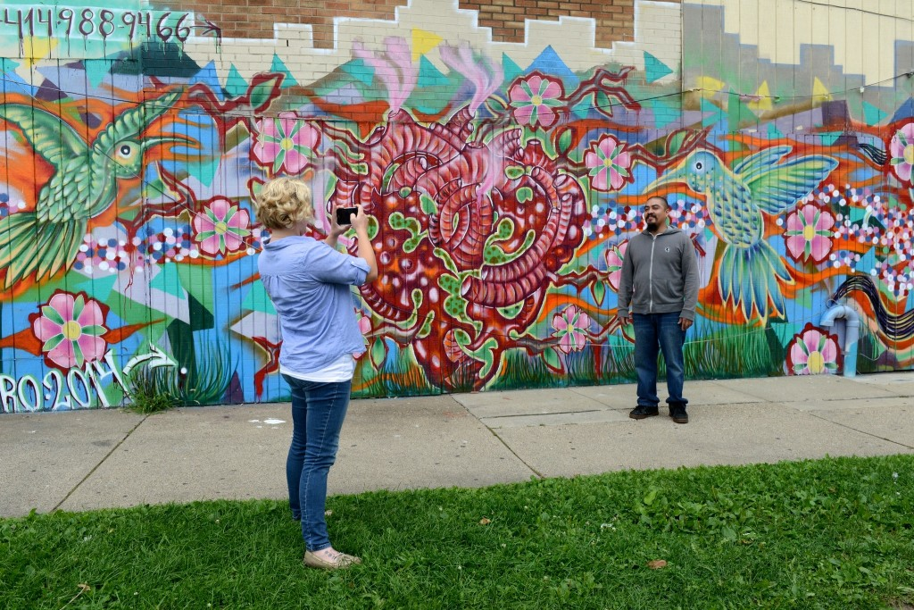 "Caitlin Sprague, creator of the Milwaukee Mural Map, photographs muralist Ramiro Sandoval Arguta in front of ""The Hummingbirds,"" at 22nd Street and National Avenue. (Photo by Sue Vliet)"