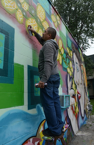 Ramiro Sandoval Arguta puts some finishing touches on his mural at 2000 W. National Ave. (Photo by Sue Vliet)