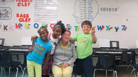 Maureen Sullivan, principal of Woodlands East, poses with students after music class. (Photo by Molly Rippinger)