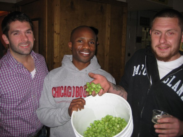 """Brett Timmerman and Patrick Awore Mutsune (left) pose at Lakefront Brewery on September 26th with a pail of hops harvested from their home at Kane Commons. Also in the photograph is Joel Franke who harvested the fragrant cones and transported them by bicycle to the brewery just downstream from the E. Kane Place development.  The limited-edition """"Fixed Gear with East Side Hippy Hops"""" beer brewed with the hops will be introduced at the brewery on Halloween from 4 to 9:30 p.m.  Photo by Michael Horne"""