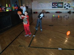 First-grade students practice throwing a football during gym class. (Photo by Raina J. Johnson)