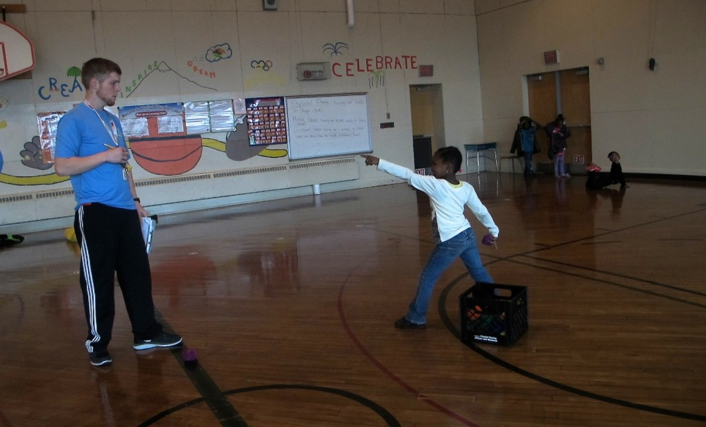 """Siefert Elementary School physical education teacher Joe Pitsch works with a first grader on his throwing skills using the """"step, point, throw"""" technique. (Photo by Raina J. Johnson)"""