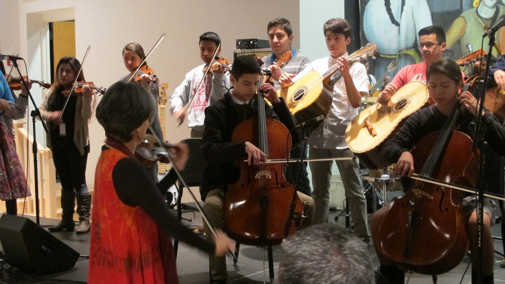 inorah Marquez conducts students in the Latino Arts Strings Program in a performance at the United Community Center. (Photo by Andrea Waxman)