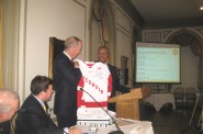 GMC Chair John Daniels presents a Wisconsin Badgers Hockey jersey signed by coach Mike Eaves to Canadian, and hockey fan, Dill Downe, CEO of BMO Harris Financial at the monthly meeting of the GMC held at the University Club Monday, November 10th, 2014. Photo by Michael Horne.