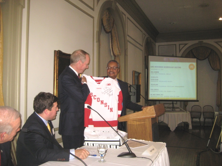 GMC Chair John Daniels presents a Wisconsin Badgers Hockey jersey signed by coach Mike Eaves to Canadian, and hockey fan, Bill Downe, CEO of BMO Harris Financial at the monthly meeting of the GMC held at the University Club Monday, November 10th, 2014. Photo by Michael Horne.