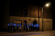 Amani United collaborated with the Overpass Light Brigade to produce a message at a recent candlelight vigil in the neighborhood. (Photo by Adam Carr)
