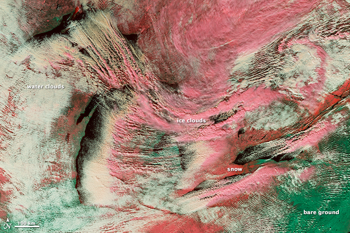 As dry, cool air rushed over the Great Lakes Nov. 18, it picked up moisture from the warmer water, creating long cloud lines known as cloud streets. In this false-color image, snow on the ground is dark pink, ice clouds are light pink and water clouds are white. Bare ground is green. Image: NASA