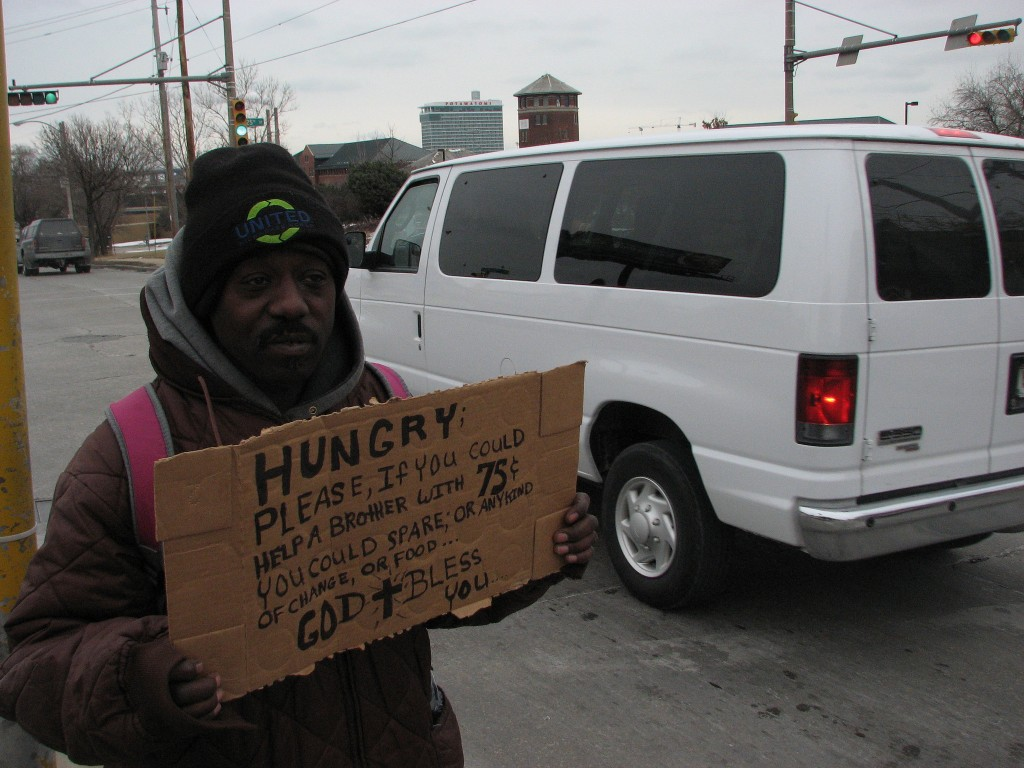 An unidentified homeless man holds a sign asking for money at 25th Street and West St. Paul Avenue. (Photo by Brendan O'Brien)
