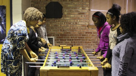 La'Ketta Caldwell joins a group of young people playing foosball in the game room at the Boys & Girls Clubs on North 6th Street. (Photo by Alhaji Camara)