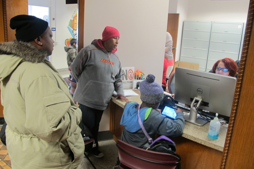 Carmeleta Harris and JaQuinn Clay wait while a Milwaukee Health Department official checks their daughter Jemiah's immunization records on the Wisconsin Immunization Registry. (Photo by Edgar Mendez)