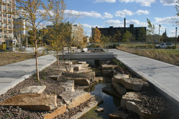 "The Reed Street Yards features two plazas (designed by noted local landscape architect Gerard Rewolinski) that take the concept of ""freshwater landscape"" to a new level, with flowing water and a water filtration system that cleans and circulates surface water from the adjacent Menomonee Canal."