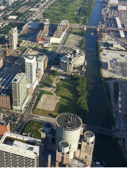 With the exception of a single building, the land bordering the South Branch of the Chicago River remains a vacant industrial wasteland. (2013)