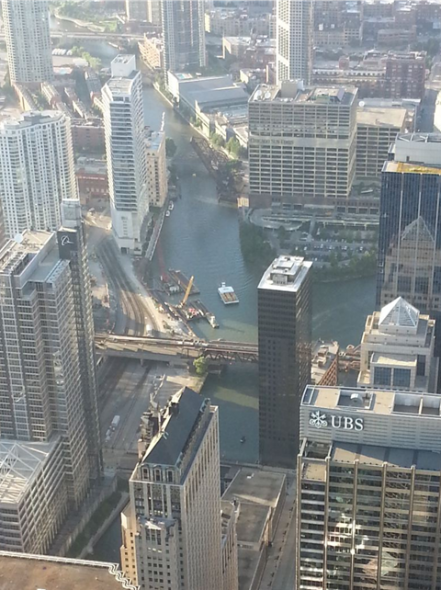 View of Wolf Point, where the North Branch of the Chicago (upper left) is joined by Lake Michigan water entering via the Main Stem (upper left) which flow then south through the South Branch lined on both sides by office towers. (2013)