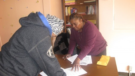 Outreach worker Shavon Pope helps a program participant update her personal information. (POutreach worker Shavon Pope helps a program participant update her personal information. (Photo by Andrea Waxman)hoto by Andrea Waxman)