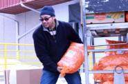 Richard Suero, pastor of Faith/Santa Fe Lutheran Church, picks up carrots and other produce at Feeding America Eastern Wisconsin. (Photo by Molly Rippinger)