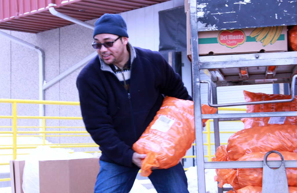 Richard Suero, pastor of Faith/Santa Fe Lutheran Church, picks up carrots and other produce at Feeding America Eastern Wisconsin. (Photo by Molly Rippinger)