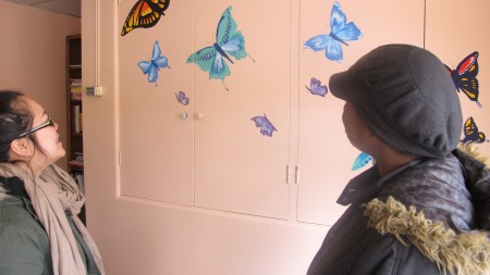 Volunteer Pang Yong Lor and outreach worker Genene Williams admire the butterflies Lor painted. (Photo by Andrea Waxman)