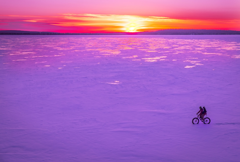 The sun sets on Winter. Here Julian Kegel rides a Badger Bikes Fattywampus across the frozen waters of Lake Superior off the tip of Roman's Point, near Cornucopia.