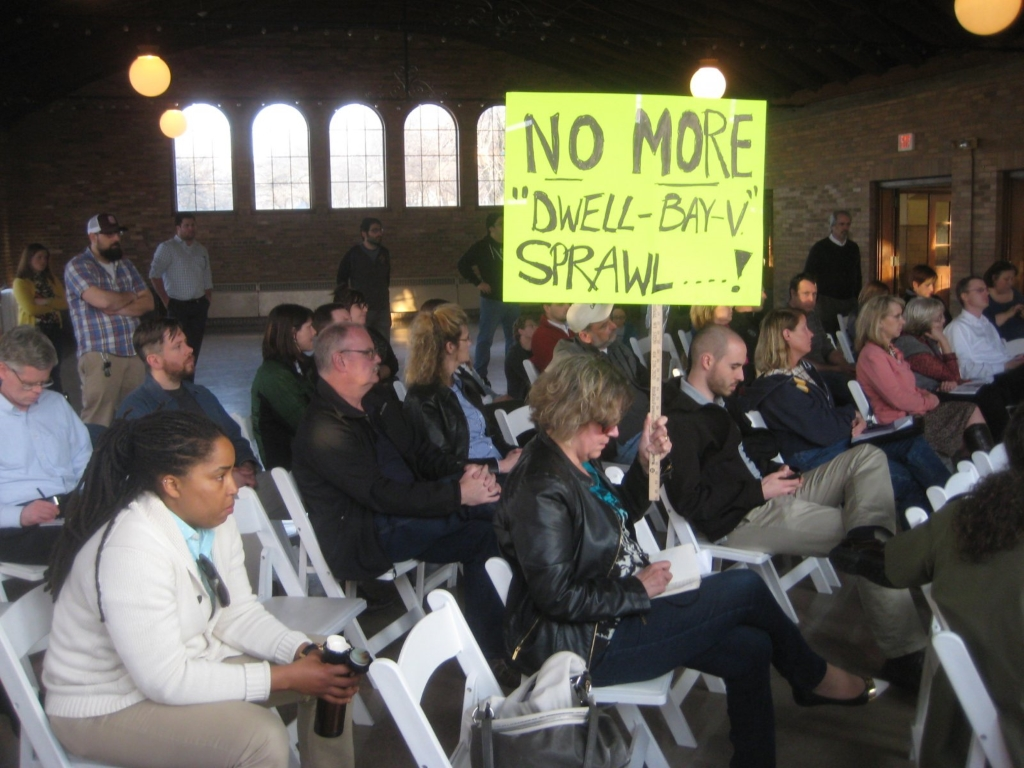 "During the neighborhood meeting one resident held a sign that said, ""NO MORE 'DWELL-BAY-V' SPRAWL....!"" Photo by Michael Horne."