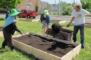 Volunteers shovel soil into a raised bed garden installed by Victory Garden Initiative. (Photo by Jennifer Reinke)