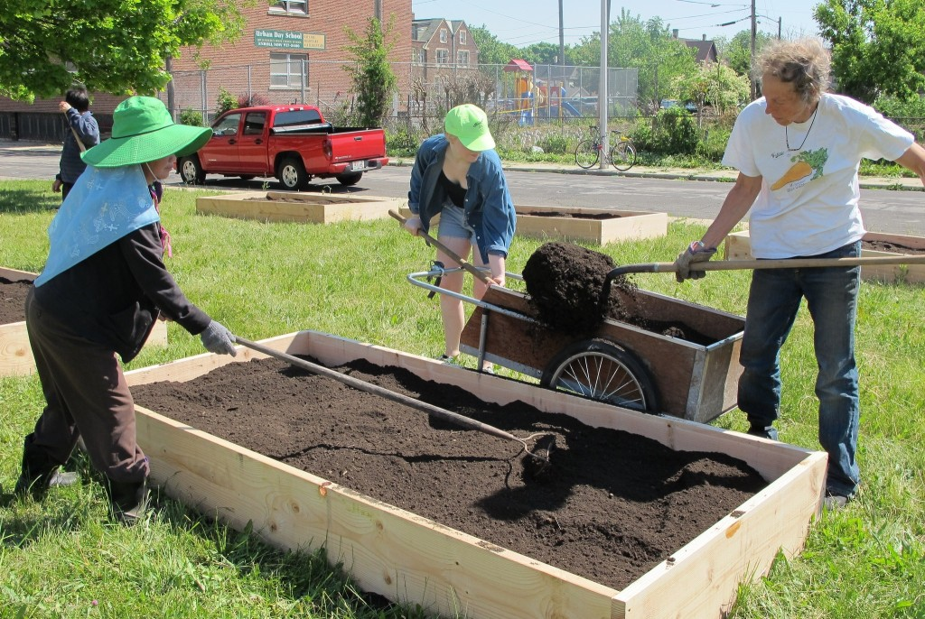Volunteers shovel soil into a raised bed garden installed by Victory Garden Initiative. (Photo by Jennifer Reinke)