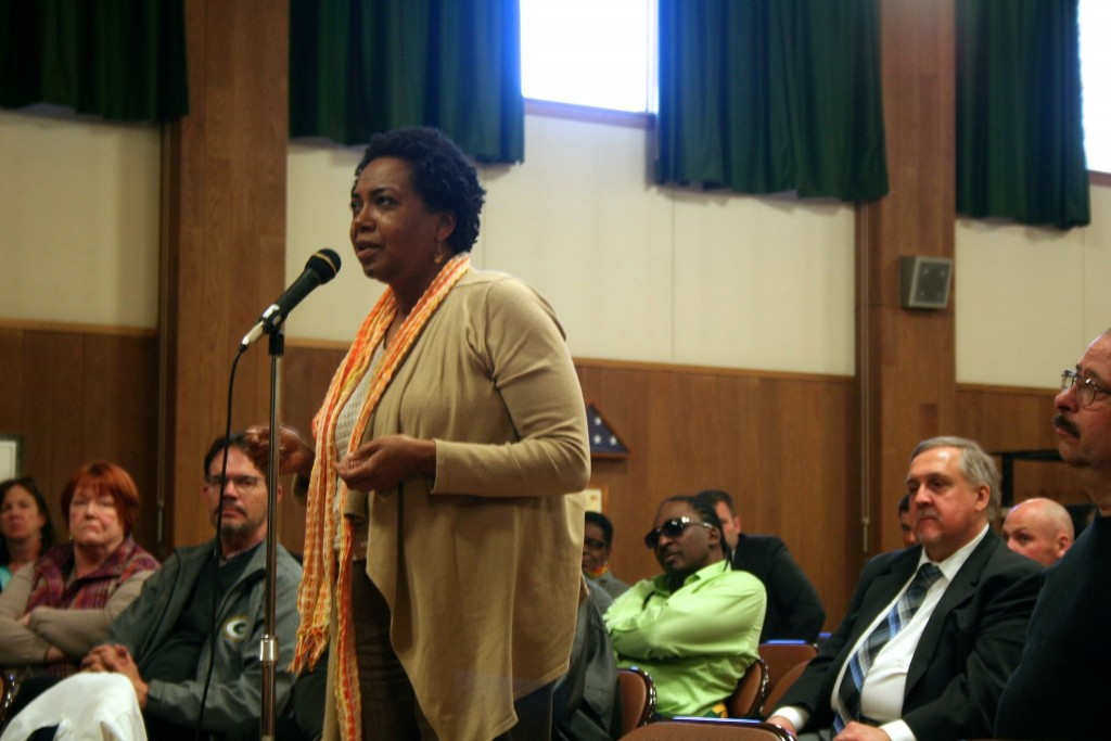Celia Jackson, 59, addresses a panel of city officials at the Washington Park Senior Center. Photo by Jabril Faraj.