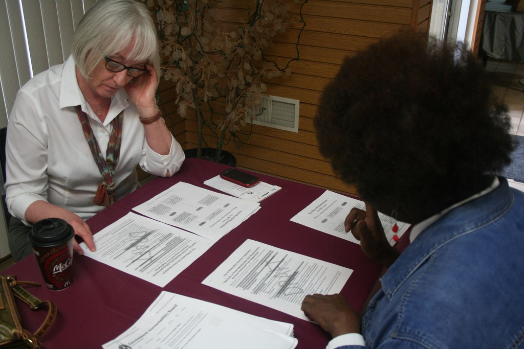 Anita Johnson (right) takes Janice Erickson through a list of voter ID requirements, as outlined by the Milwaukee Election Commission. Photo by Jabril Faraj.