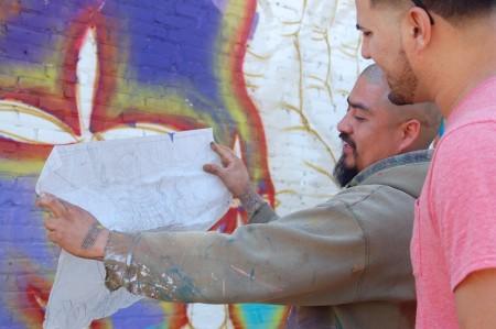 Artist Ramiro Arguta shows Eli Crespo the initial sketch of the mural's design. Photo by Devi Shastri.