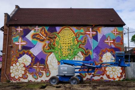 Urban artist Ramiro Arguta uses a lift to paint his mural. Photo by Adam Carr.
