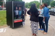 Social worker Jasmine Whiting speaks with young people passing the Children Are Not For Sale awareness campaign in front of a vending machine on North Ave. and 27th St. Photo by Allison Dikanovic.