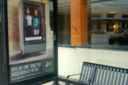 The image of young girls available for purchase covers the bus stop on 27th Street and Forest Home Drive. Photo by Allison Dikanovic.