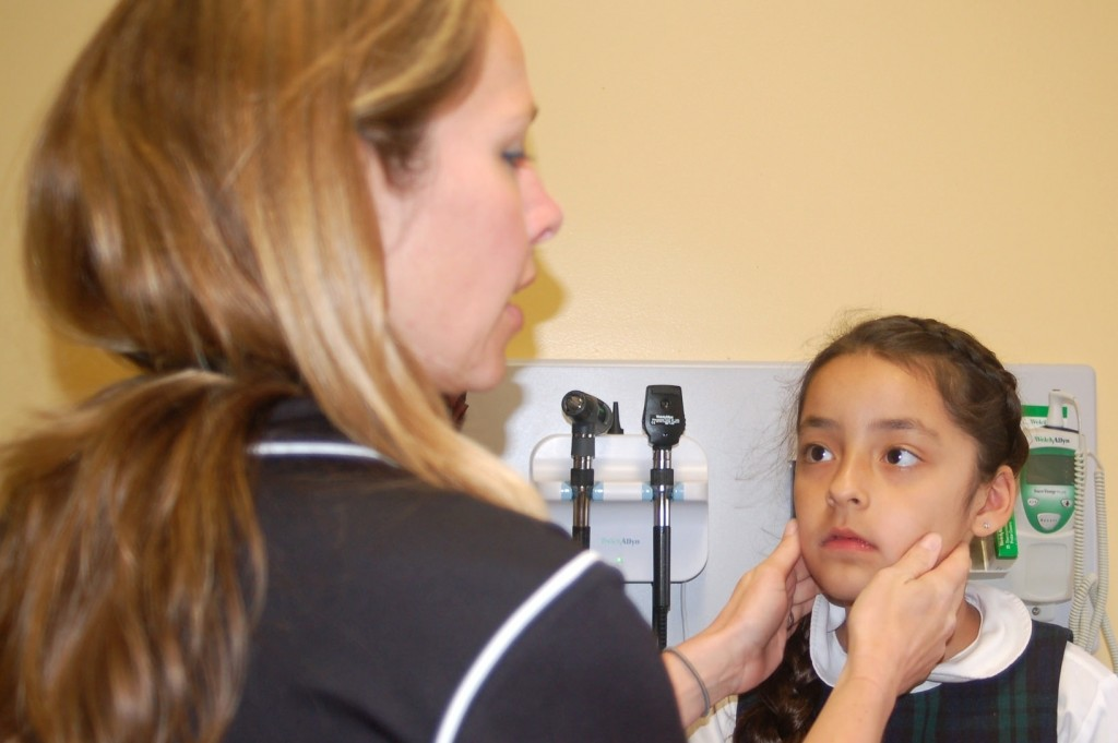 Padre Pio Clinic director Dana Rodriguez examines a second grader. Photo by Devi Shastri