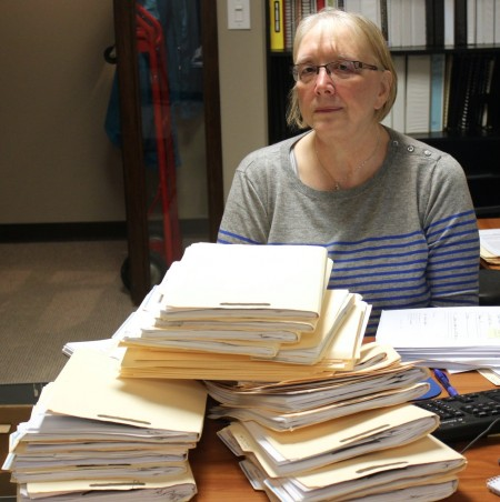 Dorothy Dean, a volunteer at Metropolitan Milwaukee Fair Housing Council, follows up on stacks of mortgage rescue scam cases. Photo by Matthew Wisla.