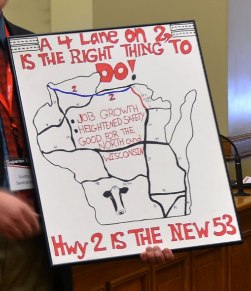 A Superior Days representative holds a sign advocating for an expansion of Highway 2 from a two-lane to a four-lane highway. Local economic development leaders say businesses interested in the region often require a four-lane highway in the area, which hurts economic growth. Photo by Madeleine Behr of the Wisconsin Center for Investigative Journalism.