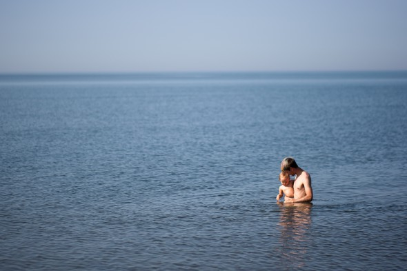 Andrew Harvey plays with his daughter in Lake Superior in July 2012. Economic development leaders in northern Wisconsin say tourism is an economic boost to the area, but the state does not offer financial assistance to tourism, retail, or hospitality businesses. Photo by Lukas Keapproth of the Wisconsin Center for Investigative Journalism.