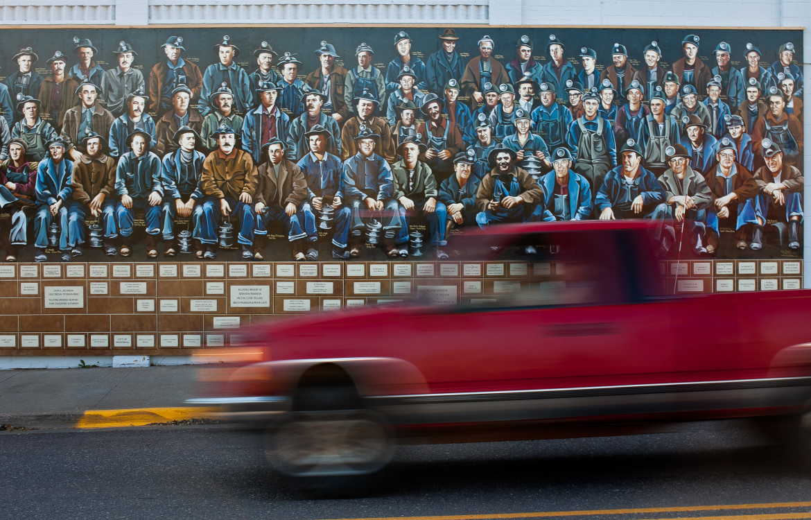 In Hurley, Wis., a truck passes a mural depicting iron ore miners in July 2012. Some residents of Iron and Ashland counties residents hoped a planned iron ore mine would bring more than 700 jobs to the area, but Gogebic Taconite pulled its plan in February 2015. Photo by Lukas Keapproth of the Wisconsin Center for Investigative Journalism.