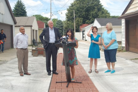Iris Gonzalez of Sixteenth Street Community Health Centers explains the impact of the green alley as Public Works Commissioner Ghassan Korban, Mayor Tom Barrett, Vicky Elkin and resident Kathie Mervyn look on. Photo by Devi Shastri.