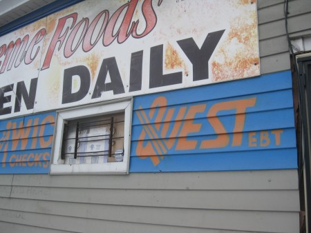 A sign promoting Quest, the state's food stamp card, is painted on the façade of a Milwaukee corner store. Photo by Brendan O'Brien.