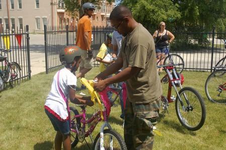 Christ Washington helps his daughter Shalisa decorate her bike. Photo by Allison Dikanovic.