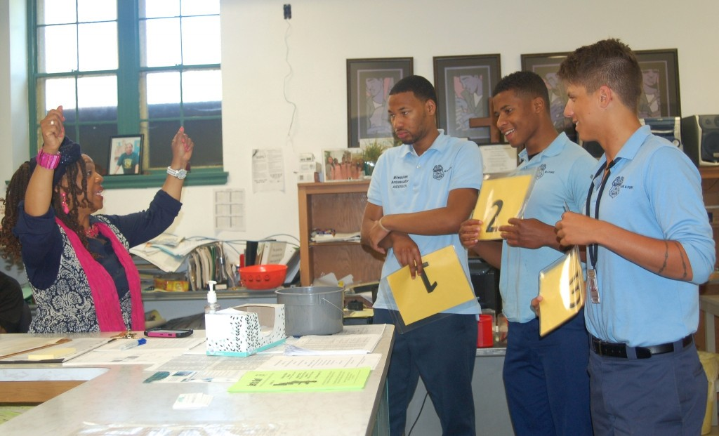 Pastor Teresa Thomas-Boyd demonstrates to Police Ambassadors Anthony Rodriguez, Kalin Welch and Michael Hendrix how to hold up numbers to call up visitors. Photo by Devi Shastri.