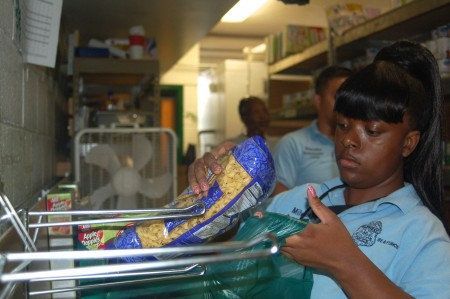 Police Ambassador Shaquirra Johnson bags pasta in the church's food pantry. Photo by Devi Shastri.